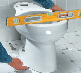 plumber placing new toilet over wax ring