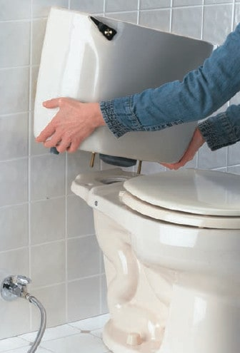 plumber placing tank over toilet bowl