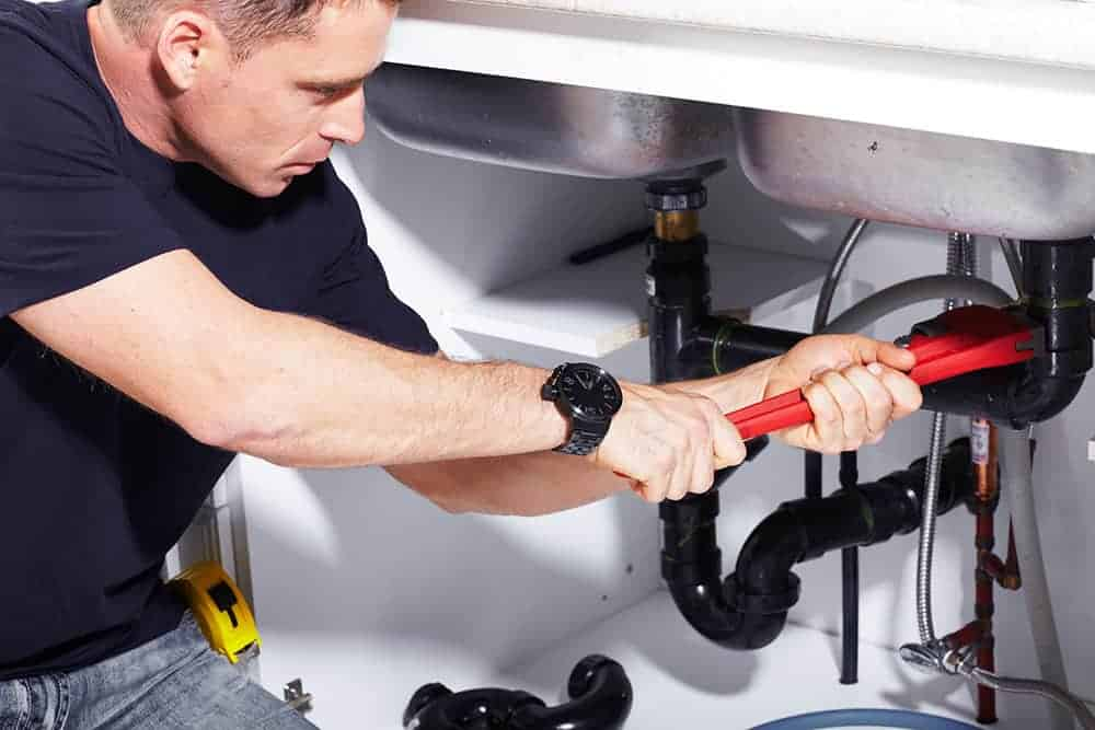 local plumber fixing pipes under the sink