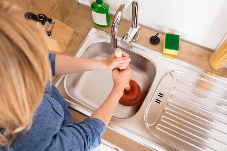 woman plunging a sink clogged with oil and fats