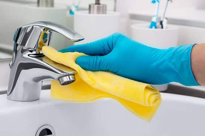 wiping down the faucet of a sink