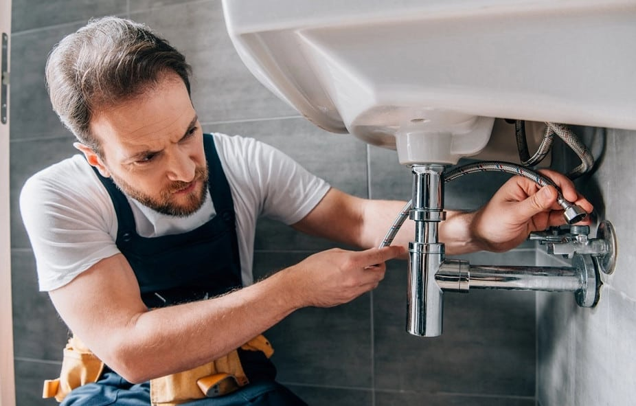 local plumber in sydney working on fixing a pipe under the basin